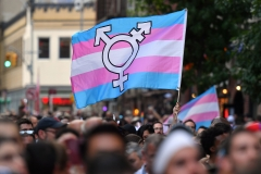 A transgender flag is brandished at a protest. (Photo credit: ANGELA WEISS/AFP via Getty Images)