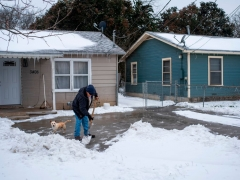 A Waco, Texas, resident clears snow from his driveway alongside his dog on February 17, 2021 as severe winter weather conditions over the last few days has forced road closures and power outages over the state. (Photo by MATTHEW BUSCH/AFP via Getty Images)