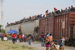 Central American immigrant get on the so-called La Bestia (The Beast) cargo train, in an attempt to reach the Mexico-US border, in Arriaga, Chiapas state, Mexico on July 16, 2014. (Photo by ELIZABETH RUIZ/AFP via Getty Images)