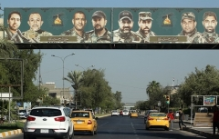 A propaganda banner eulogizing Katai'b Hezbollah fighters hangs over a street in central Baghdad. (Photo by Ahmad al-Rubaye/AFP via Getty Images)