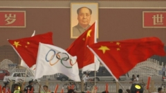 The giant portrait on Mao Zedong on Tiananmen Gate overlooks people waving Chinese and Olympic flags ahead of Beijing's hosting of the summer games, in 2008.  (Photo by Peter Parks/AFP via Getty Images)