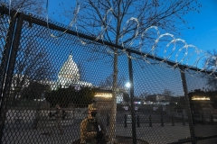 National Guard troops stand behind a security fence topped by concertina wire surrounding the grounds of the U.S. Capitol. (Photo by ROBERTO SCHMIDT/AFP via Getty Images)