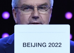 At an International Olympic Committee meeting in 2015, IOC president Thomas Bach shows the card with the winning bid for the Winter Olympic host city for 2022. (Photo by Manan Vatsyayana/AFP via Getty Images)