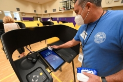 Election official Horacio Rameriz disinfects a voting machine between users as people cast their ballots for the US presidential election at Horace Mann Elementary School on October 30, 2020 in Beverly Hills, California. (Photo by ROBYN BECK/AFP via Getty Images)