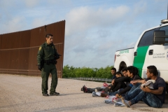 - A Border Patrol agent apprehends illegal immigrants shortly after they crossed the border from Mexico into the United States on Monday, March 26, 2018 in the Rio Grande Valley Sector near McAllen, Texas. (Photo by LOREN ELLIOTT/AFP via Getty Images)