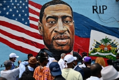 People gather at the unveiling of artist Kenny Altidor's memorial portrait of George Floyd. (Photo credit: ANGELA WEISS/AFP via Getty Images)