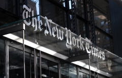 The corporate logo of the New York Times hangs above the front door of their headquarters on Oct. 23, 2018 in New York City. (Photo credit: Gary Hershorn/Getty Images)
