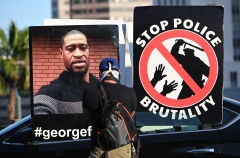 Featured are police brutality protest signs featuring George Floyd and a police officer. (Photo credit: ROBYN BECK/AFP via Getty Images)