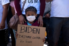 A Honduran girl holds a sign asking President Biden to let her into the U.S. during a rally at the San Ysidro crossing port in Tijuana, Mexico on March 2, 2021. (Photo by GUILLERMO ARIAS/AFP via Getty Images)