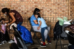 Migrants from Central America wait for a bus after they are dropped off by the US Customs and Border Protection at a bus station in Brownsville, Texas, on March 15, 2021. (Photo by CHANDAN KHANNA/AFP via Getty Images)