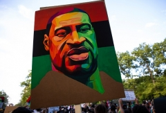 A poster featuring the late George Floyd waves over a June 19, 2020 protest march in Brooklyn, N.Y.  (Photo by Robert Nickelsberg/Getty Images)