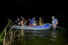 A human smuggler guides an inflatable boat carrying would-be asylum seekers from Central America across the Rio Grande River at the border city of Roma on March 29, 2021. (Photo by ED JONES/AFP via Getty Images)
