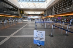 A sign advises travelers to respect social distancing at a largely empty Tom Bradley International Terminal at Los Angeles International airport on August 12, 2020 in Los Angeles during the coronavirus pandemic. (Photo by ROBYN BECK/AFP via Getty Images)