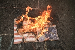 An American flag burns on the ground. (Photo credit: Diego Cuevas/Vizzor Image/Getty Images)