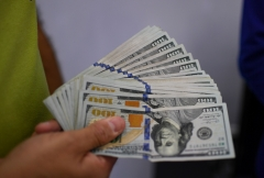 A man holds dollar bills. (Photo credit: YURI CORTEZ/AFP via Getty Images)