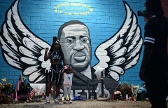 People stand in front of a mural of George Floyd in Houston, Tex. on June 8, 2020. (Photo credit: JOHANNES EISELE/AFP via Getty Images)