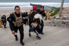 A Central American migrant is taken into custody by Tijuana police after migrants faced US Border Patrol agents while trying to cross the US-Mexico border fence from Tijuana to San Diego, as seen from Playas de Tijuana, in Baja California state, Mexico, on March 21, 2019. (Photo by GUILLERMO ARIAS/AFP via Getty Images)