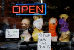 Mannequin heads wear masks in the window of a small boutique advertising availability of masks, gloves, and other pandemic necessities amid the Coronavirus outbreak in Arlington, Virginia, on April 27, 2020.  (Photo by OLIVIER DOULIERY/AFP via Getty Images)