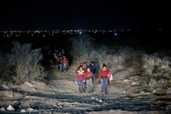 In a photo taken on March 27, 2021 immigrants, who arrived illegally across the Rio Grande river from Mexico, make their way along a track towards a processing checkpoint set up by border patrol agents in the border city of Roma. (Photo by ED JONES/AFP via Getty Images