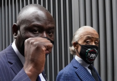 Attorney Benjamin Crump (L) holds up his fist as he walks with Reverend Al Sharpton after holding a press conference during the National Action Network(NAN) Virtual Convention 2021 in New York on April 14, 2021. (Photo by TIMOTHY A. CLARY/AFP via Getty Images)
