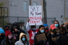 People hold signs as they gather for a vigil in Columbus, Ohio on April 21, 2021 in memory of MaKhia Bryant, 16, who was shot and killed by a Columbus Police Department officer. (Photo by JEFF DEAN/AFP via Getty Images)