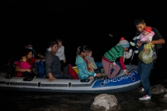 Guided by coyotes piloting an inflatable raft, migrants cross the Rio Grande River and arrive on American soil on April 23, 2021 in Roma, Texas. After crossing onto the shallow banks, the migrants hike half a mile through sandy gullies and shrub covered land towards waiting Border Patrol officers for processing and detention. (Photo by Benjamin Lowy/Getty Images)