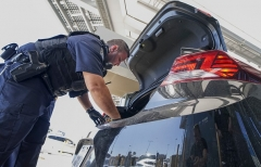 An Immigration and Customs Enforcement agent checks a vehicle for contraband at the San Ysidro port of entry in San Ysidro, Calif. (Photo by Sandy Huffaker/AFP via Getty Images)