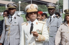 Libyan Head of State Colonel Moamer Kadhafi (C) reviews troops 03 December 1985 in Dakar upon his arrival for three-day official visit to Senegal. (Photo credit: JOEL ROBINE/AFP via Getty Images)