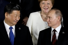 German Chancellor Angela Merkel stands behind Russian President Vladimir Putin and Chinese President Xi Jinping as they arrive to pose for a group photo before a cultural event at the Osaka Geihinkan in Osaka Castle Park during the G20 Summit in Osaka on June 28, 2019. (Photo credit: DOMINIQUE JACOVIDES/AFP via Getty Images)