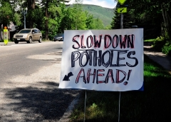 A hand-lettered, homemade sign warns Aspen, Colorado, motorists of pot holes ahead. (File Photo by Robert Alexander/Getty Images)