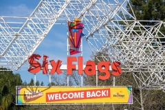 A sign at the entrance of the theme park Six Flags Magic Mountain welcomes the public back on the day of the park's re-opening, April 1, 2021, in Valencia, California. (Photo by VALERIE MACON/AFP via Getty Images)