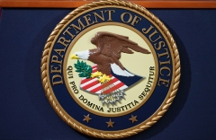 The Department of Justice seal is seen on a lectern ahead of a press conference. (Photo credit: MANDEL NGAN/AFP via Getty Images)