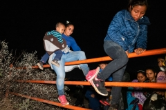 Migrants scale a cattle fence on private property after arriving on the American shores of the Rio Grande River on April 24, 2021 in Roma, Texas. Guided by coyotes piloting an inflatable raft, migrants cross the Rio Grande River and arrive on American soil. (Photo by Benjamin Lowy/Getty Images)