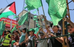 Palestinian children wave flags of the Hamas terrorist group in Rafah in the Gaza Strip last July. (Photo by Said Khatib/AFP via Getty Images)
