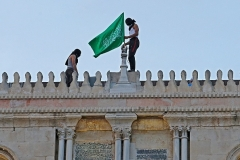 Palestinians hoist the flag of the Hamas terrorist group on Monday atop Jerusalem's al-Aqsa mosque, the third-holiest site in Islam. (Photo by Ahmad Gharabli/AFP via Getty Images)