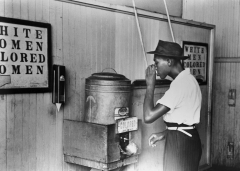 A black man drinks at a segregated water fountain during the Jim Crow era. (Photo credit: Bettmann/Contributor/Getty Images)