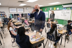 President Joe Biden points to his hair after a student told him she wanted to be a hairstylist when she grows up. (Photo credit: MANDEL NGAN/AFP via Getty Images)