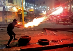 A Palestinian launches flares amid clashes with Israeli soldiers in the city center of Hebron. (Photo credit: HAZEM BADER/AFP via Getty Images)