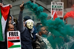 Palestinian flags, smoke flares and placards featured at a demonstration in London on Saturday. (Photo by Tolga Akmen/AFP via Getty Images)