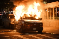 An NYPD vehicle burns during the riots after the death of George Floyd. (Photo credit: Kevin Mazur/Getty Images)