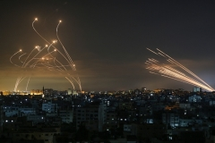 A barrage of rockets fired towards Israel from Gaza early on Friday, right, confronted by Israel's Iron Dome aerial defence system. (Photo by Anas Baba/AFP via Getty Images)