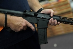 A customer handles an AR-15 at a sports shop in New York. (Photo by TIMOTHY A. CLARY/AFP via Getty Images)