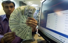 A man holds up a plethora of dollar bills. (Photo credit: AAMIR QURESHI/AFP via Getty Images)
