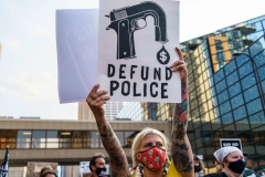 """A Protester hold a sign reading """"Defund the Police"""" outside Hennepin County Government Plaza during a demonstration against police brutality and racismon August 24, 2020 in Minneapolis, Minnesota. - It was the second day of demonstrations in Kenosha after video circulated Sunday showing the shooting of Jacob Blake -- multiple times, in the back, as he tried to get in his car, with his three children watching. (Photo by KEREM YUCEL/AFP via Getty Images)"""