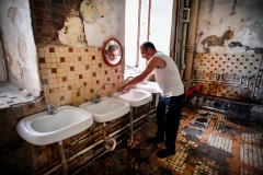 Vladimir Mogilnikov, 62, washes his hands in a communal washing room in a dormitory for the workers of Proletarka textile factory in the town of Tver, 200 kilometres north-west from Moscow on August 8, 2020. (Photo by ALEXANDER NEMENOV/AFP via Getty Images)