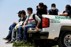 Migrants attempting to cross in to the U.S. from Mexico are detained by U.S. Customs and Border Protection at the border May 21, 2021 in San Luis, Arizona. (Photo by Nick Ut/Getty Images)