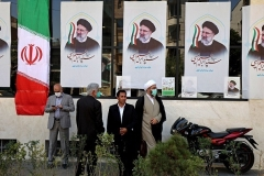 Iranians stand in front of a campaign office displaying posters for presidential candidate Ebrahim Raisi in Tehran. (Photo by Atta Kenare/AFP via Getty Images)