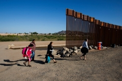Migrants from Colombia walk around an unfinished section of border wall near Yuma, Arizona last month. (Photo by RINGO CHIU/AFP via Getty Images)
