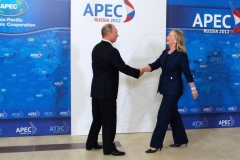 Then-Secretary of State Hillary Clinton shakes hands with Russia's President Vladimir Putin at the Asian-Pacific Economic Cooperation (APEC) Summit in Vladivostok on September 8, 2012. (Photo by MIKHAIL KLIMENTYEV/AFP/GettyImages)