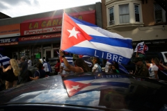 People wave Cuban flags as they drive down a road during a protest showing support for Cubans demonstrating against their government, in Union City, New Jersey, on July 18, 2021. (Photo credit: KENA BETANCUR/AFP via Getty Images)